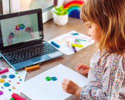 Little girl molding colorful clay cloud with rain watching online learning lesson on the laptop indoor. Distance home learning concept.